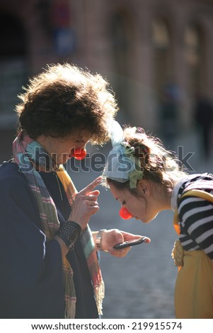 Two curious clowns exploring smart phone, street theater concept - stock photo
