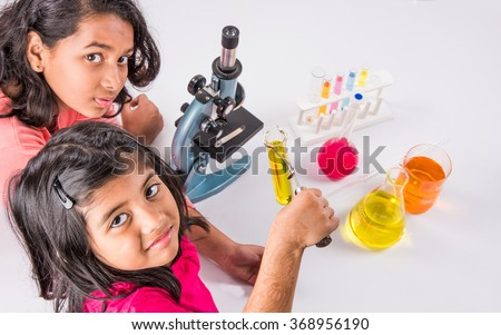 two curious indian girls with microscope, 2 asian girls with microscope, Cute little girls holding microscope, small indian girls and science experiment, girls doing science experiments, science lab - stock photo