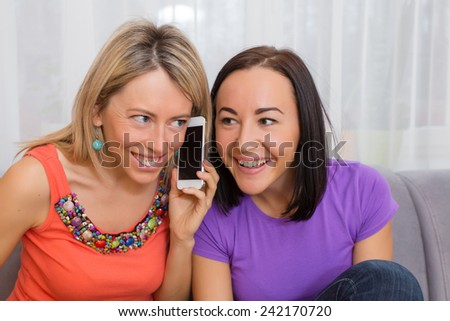 Two curious women listening to phone conversation - stock photo