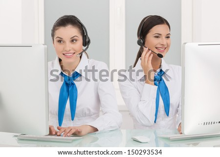 Two customer service representatives at work. Two cheerful young female customer service representatives in headset working at the computer and smiling - stock photo