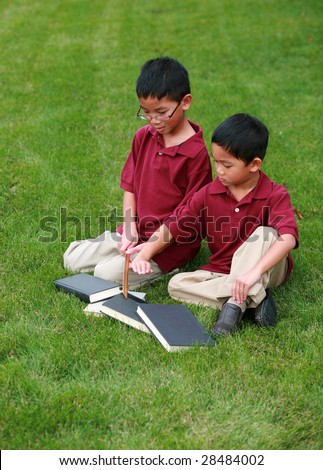 two cute asian boys reading in grass