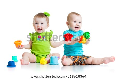 Two cute babies playing with color toys. Children girl and boy sitting on floor. Isolated on white background.