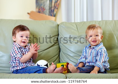 two cute baby boys playing with toys at home - stock photo