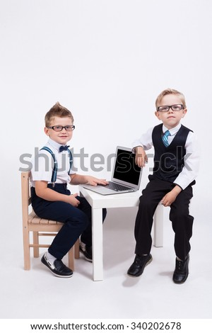 Two cute baby business in the form of business with the glasses on the eyes sitting at the table with a laptop and smiling at the camera.