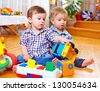 two cute baby toddlers playing in nursery room - stock photo