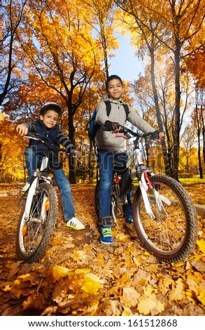 Two cute black smiling 8 and 10 years old boys ride bicycles, wearing helmet in the autumn maple and oak tree park