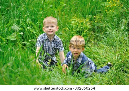 Two cute blonde boys dressed in a plaid shirt hidden in lush green tall grass