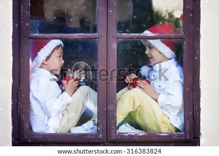 Two cute boys, brothers looking through a window, holding cups with tea, waiting for Santa - stock photo