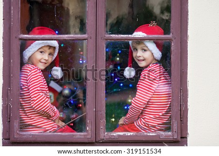 Two cute boys, brothers, looking through a window, waiting impatiently for Santa, Christmas concept - stock photo