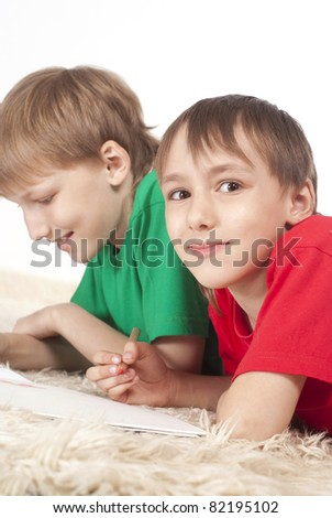 two cute boys drawing on a carpet