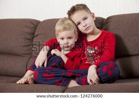 Two cute boys in pajamas sitting on the sofa embracing and looking in the camera - stock photo