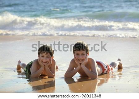 two cute boys laying at the beach