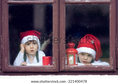 Two cute boys, looking through a window, waiting for Santa - stock photo