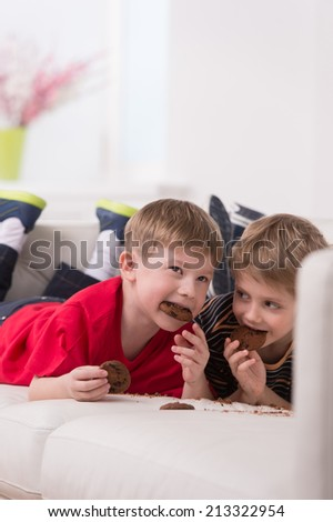 two cute boys lying on couch. two friends eating cookies and resting - stock photo