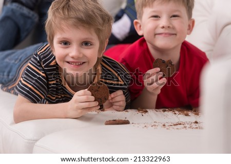 two cute boys lying on couch. two friends eating cookies and smiling