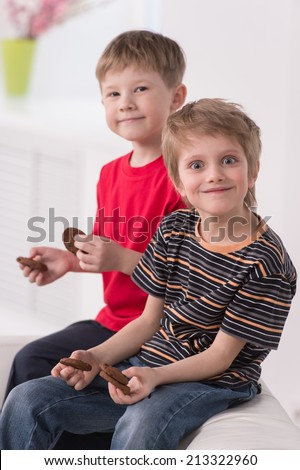 two cute boys sitting on couch. two friends eating cookies and posing - stock photo