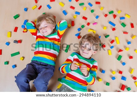 Two cute brothers, little children playing with lots of colorful wooden blocks indoor. Active kid boy wearing colorful shirt and having fun with building and creating. - stock photo