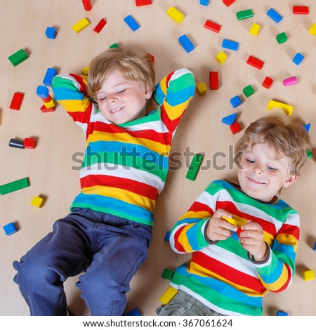 Two cute brothers, little children playing with lots of colorful wooden blocks indoor. Active kid boy wearing colorful shirt and having fun with building and creating.