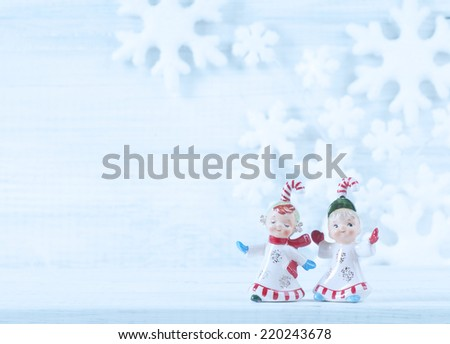 Two Cute Candy Cane Kid ceramic figurines from 1950s on Rustic White Wood Shelf and Background with Snowflakes Behind with blank room or space for copy, text, your words.  Faded frosty blue tint  - stock photo