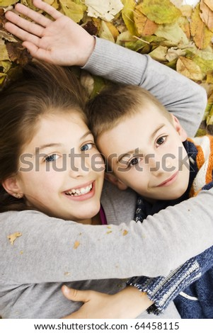 Two cute caucasian kids lying down with leaves around