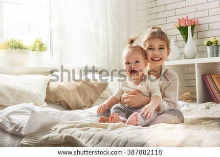 two cute child baby girls playing and having fun on the bed. loving sisters hug - stock photo