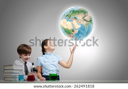 Two cute children at chemistry lesson making experiments. Elements of this image are furnished by NASA