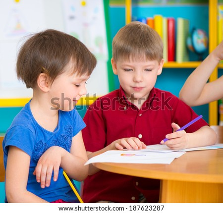 Two cute children drawing with colorful pencils at kindergarten