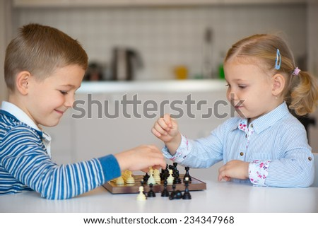 Two cute children playing chess at home - stock photo