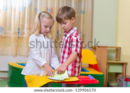 Two cute children playing with iron at home - stock photo
