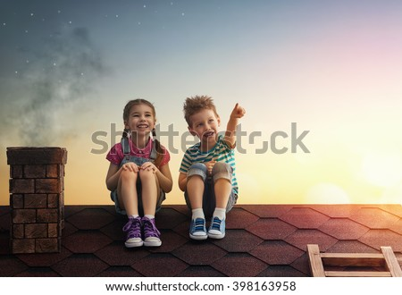 Two cute children sit on the roof and look at the stars. Boy and girl make a wish by seeing a shooting star. - stock photo