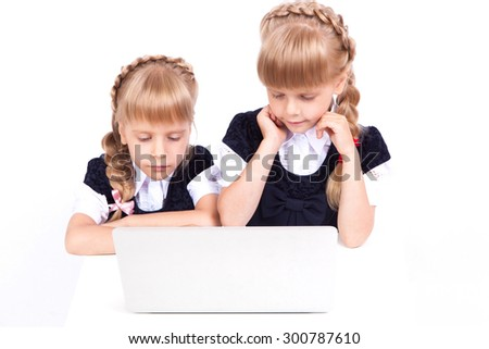 Two cute curious girl twins on a white background looking at a laptop in fancy dresses. The picture with depth of field - stock photo