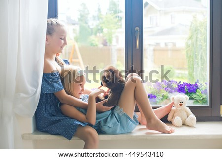 Two cute european toddler girls sitting on sill near window at home playing teddy bears happy and funny. Colorful back yard at background - stock photo