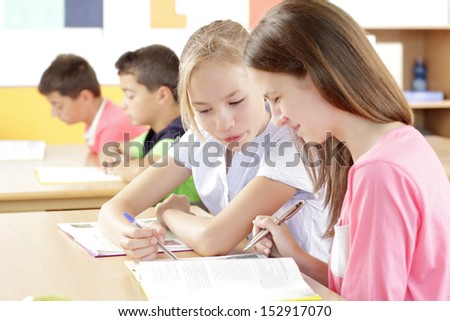 Two cute girl working in class