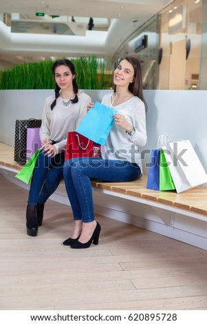 Two cute girls are sitting on a bench in the mall with gift bags . After shopping. To make purchases