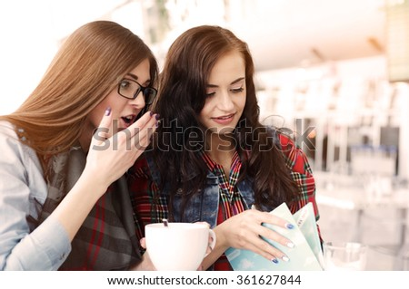 Two cute girls having a break time in cafe.  Brunette girl opening menu setor creative handmade card. Hanging out.   - stock photo