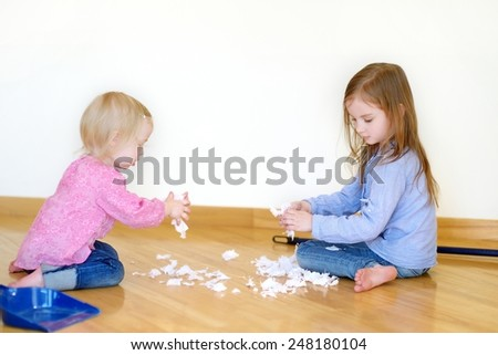 Two cute girls helping her mom to clean up at home - stock photo