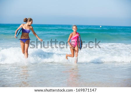 Two cute girls in bikini with surfboard running from the ocean