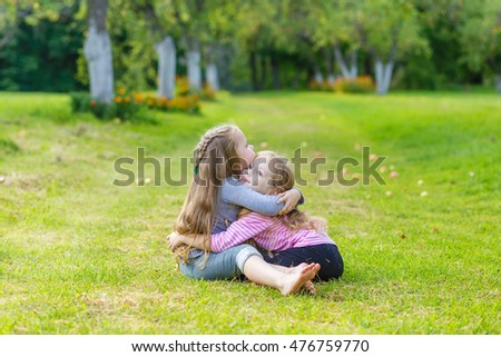 Two cute girls playing in the park a beautiful sunny day. Girls relaxing in the garden