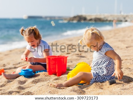 Two cute girls playing on the beach