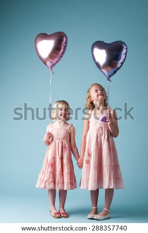 Two Cute Girls playing with Balloons - stock photo