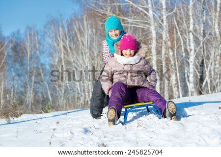 Two cute girls riding sled and having fun - stock photo