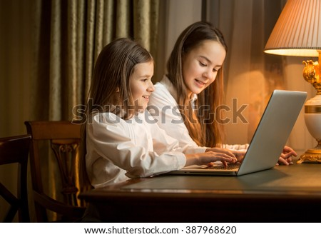 Two cute girls sitting at table and using laptop
