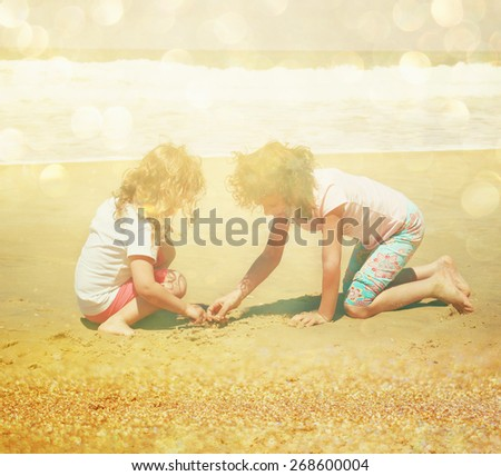 two cute happy kids (girls) playing at the beach. toned image with glitter overlay  - stock photo