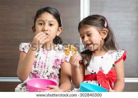 Two cute Indian girls eating food. Asian sibling or children enjoying traditional snack murukku, living lifestyle at home. - stock photo