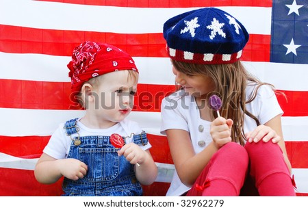 Two cute kids eating suckers by an american flag - stock photo