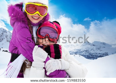 Two cute kids friends girls hugging with skis and mountain on background - stock photo
