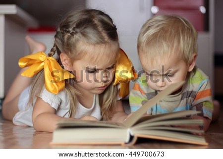 Two cute kids, girl with yellow bows and small toddler boy, sister and brother, lying on the floor and reading a book attentively, seriously and concentrated, portrait, school and education concept