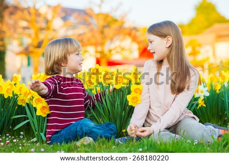 Two cute kids, little boy and his big sister, playing in the park between yellow daffodils flowers at sunset - stock photo