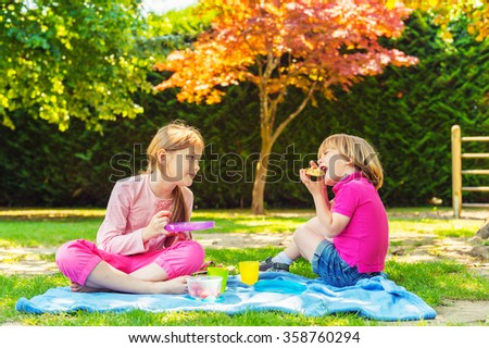 Two cute kids, little girl and her brother, having a picnic outdoors in the park - stock photo