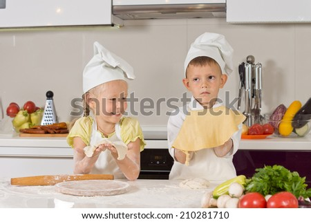 Two Cute Kids Showing Dough They Made at the Kitchen.